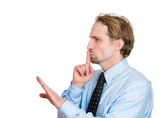 Be quiet. Side view man with finger on lips, silence gesture