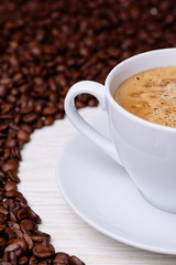 white cup of coffee on a background of coffee beans