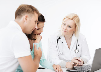 doctor with patients looking at laptop
