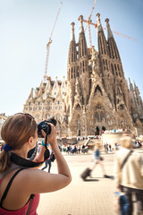 Young woman taking picture of Sagrada Familia.