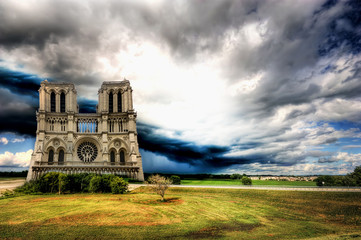 Notre Dame cathedral of Paris in an open field under storm