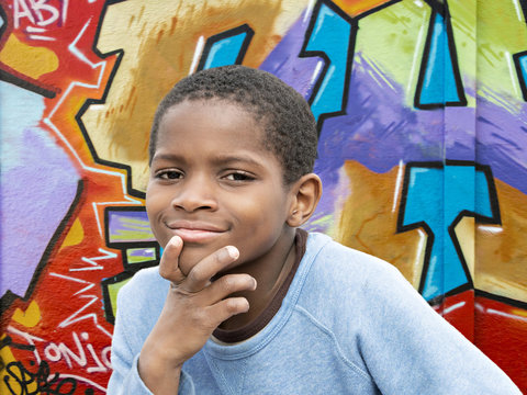Young Afro boy in front of a graffiti wall
