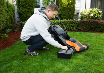 Wall Mural - Mature man putting battery into electric Lawn Mower
