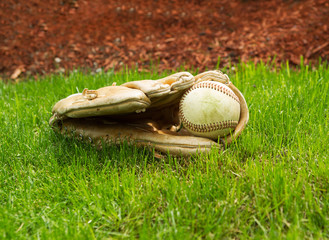 Old Baseball inside Used Glove on ground
