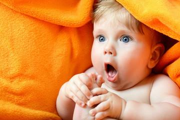 portrait of cute baby boy lying on orange plaid and sucking his