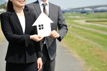 家を紹介する男女のビジネスマン