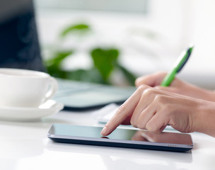 Woman hands with tablet PC and notepad at office