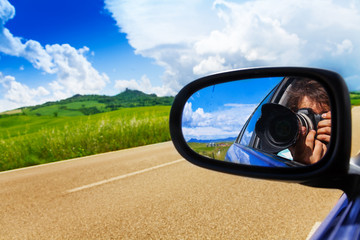 Photographer in car mirror drives near valley