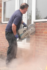A window fitter using a disc cutter on brickwork