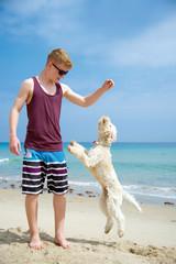 Teenager mit seinem Hund am Strand