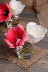 Beautiful tulips in bucket in vase on table on grey background