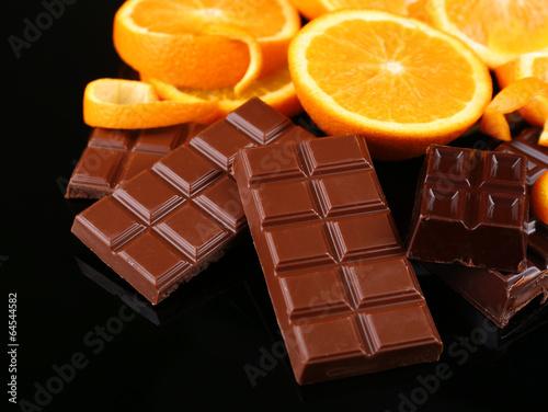 Fototapete Chocolate and orange on black background