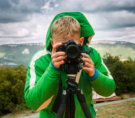 Photographer shoots with DSLR Camera using tripod