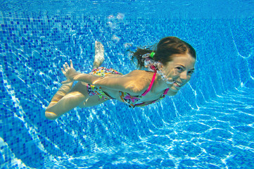 Happy active underwater girl swims in pool and having fun