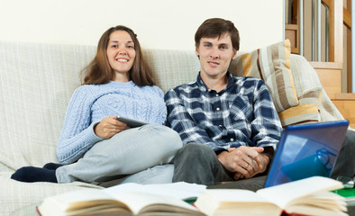 Two students with books and laptop sitting on the sofa