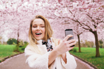 Happy young woman photographing herself at park