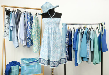 Wardrobe with blue clothes,summer dress with hat on a mannequin.