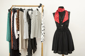 Wardrobe with polka dots clothes and outfit on mannequin.