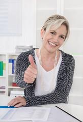 Glückliche ältere Frau im Büro mit Daumen hoch