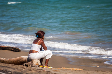 Sad cuban woman sitting on beach