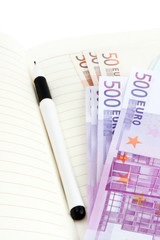 Euro banknotes, notebook and pen
