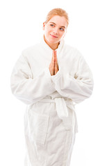 Young woman standing in bathrobe in prayer position