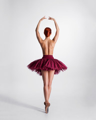 Young naked redhead female ballet dancer in a studio