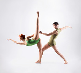 Couple of gymnasts training in a studio