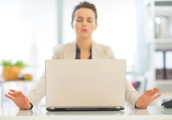 Closeup on laptop and relaxing business woman in background Wall mural