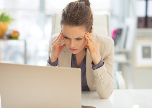 Stressed business woman with laptop at work