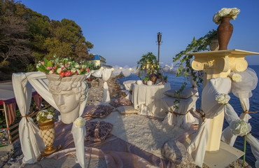 Romantic decoration of table for two on the sea shore.