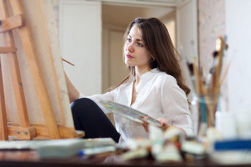 Long-haired woman paints picture on canvas