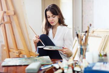 beautiful artist paints on canvas