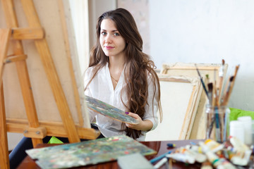 Long-haired  artist paints picture on canvas