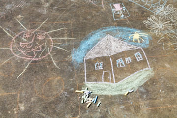 child drawing - house and sun painted on asphalt