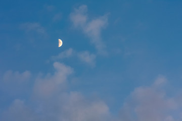 Moon on blue sky with pink clouds