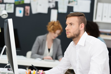 mann arbeitet konzentriert am pc
