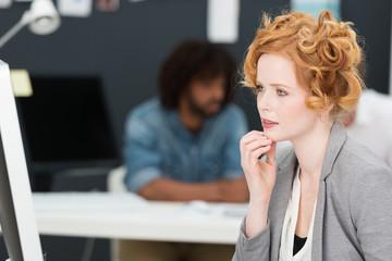 geschäftsfrau schaut nachdenklich auf computer