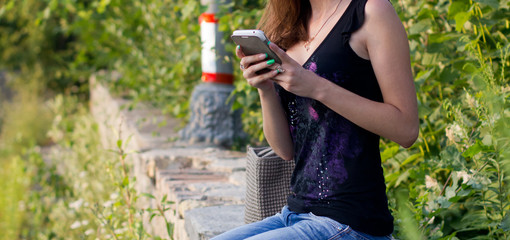 In the park girl with mobile phone sits on the curb
