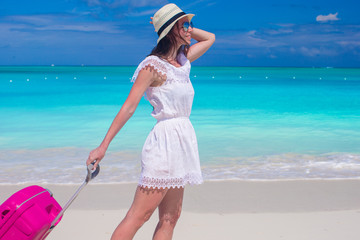 Young beautiful woman walking with her luggage on tropical beach