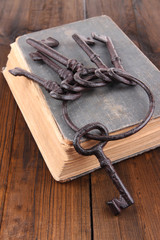 Old keys on old book on wooden background
