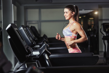 Young sporty woman run on machine in the gym