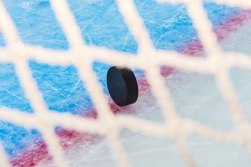 Hockey puck through goal net