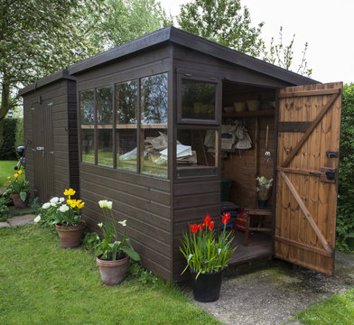 Garden shed with door open, tools, flowers, and plant pots.