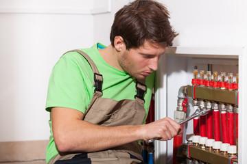 Repairman fixing valves in home