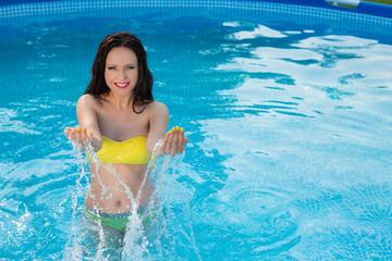 woman posing in her bikini in the swimming-pool