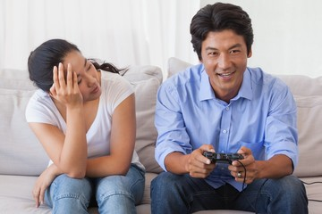 Man ignoring his girlfriend playing video games