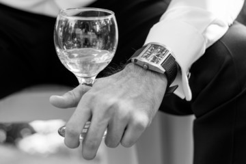Closeup of groom and business man with glass of wine and watch