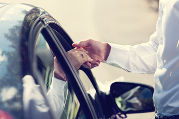 Gentle holding hands near car with wedding couple with ring