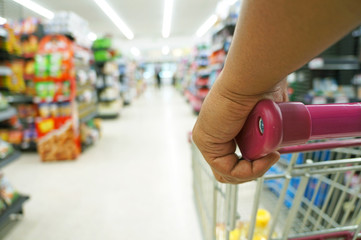 Closeup hand on shopping cart at supermarket